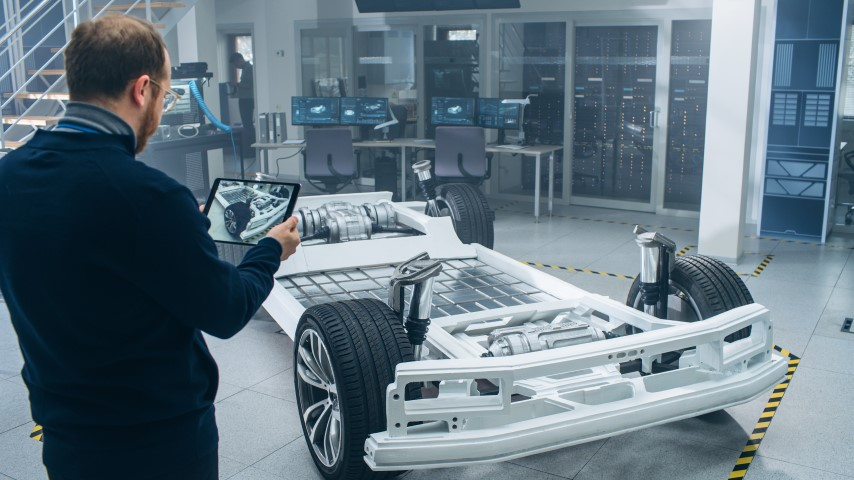 Engineer with Glasses and Beard Scans Electric Car Chassis Prototype with Wheels, Batteries and Engine with an Augmented Reality Software on a Tablet Computer in a High Tech Development Laboratory.